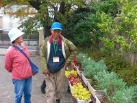 正門付近に並ぶ植物を説明する北居重信さん